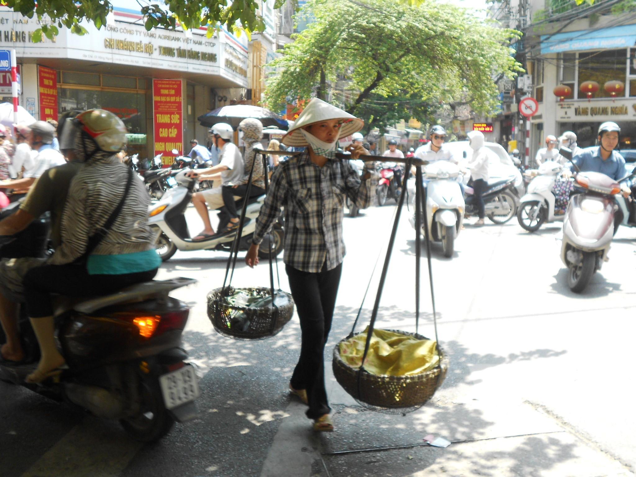 Mujer con sombrero cónico y pértiga de bambú con dos cestos